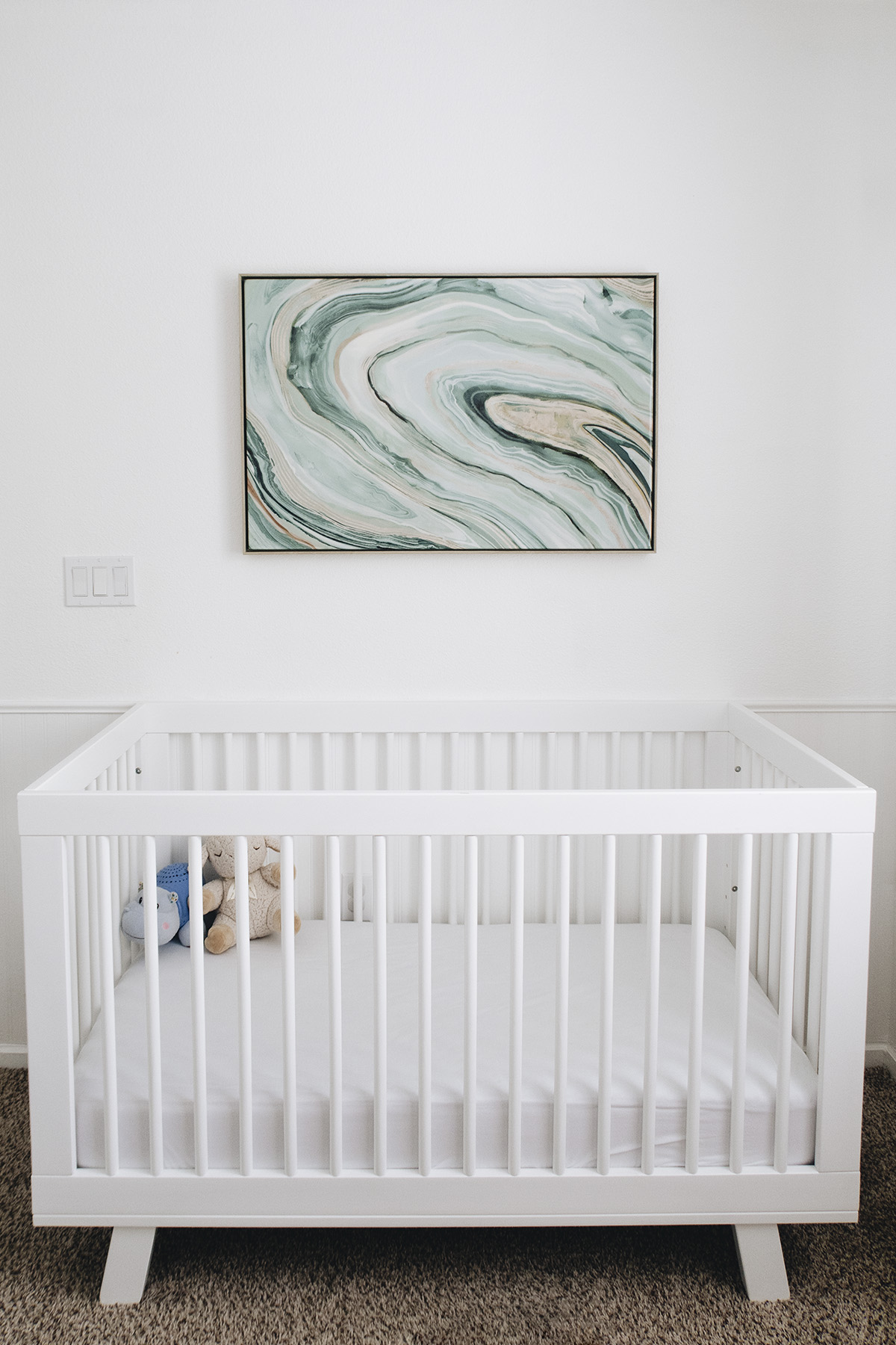 modern artwork on top of a white modern crib