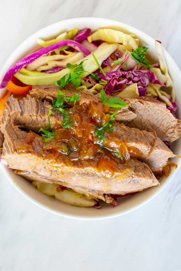 Brisket served with cabbage on a white bowl