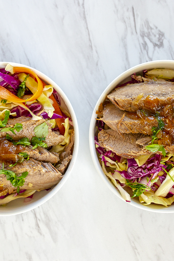 Beef brisket served on top of cabbage slaw on two bowls