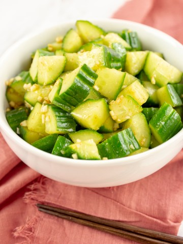 Chinese cucumber salad on white bowl on top of pink napkin