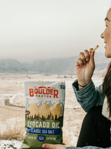 Woman eating potato chips outdoors in the snow overlooking the Flatirons in Boulder Colorado
