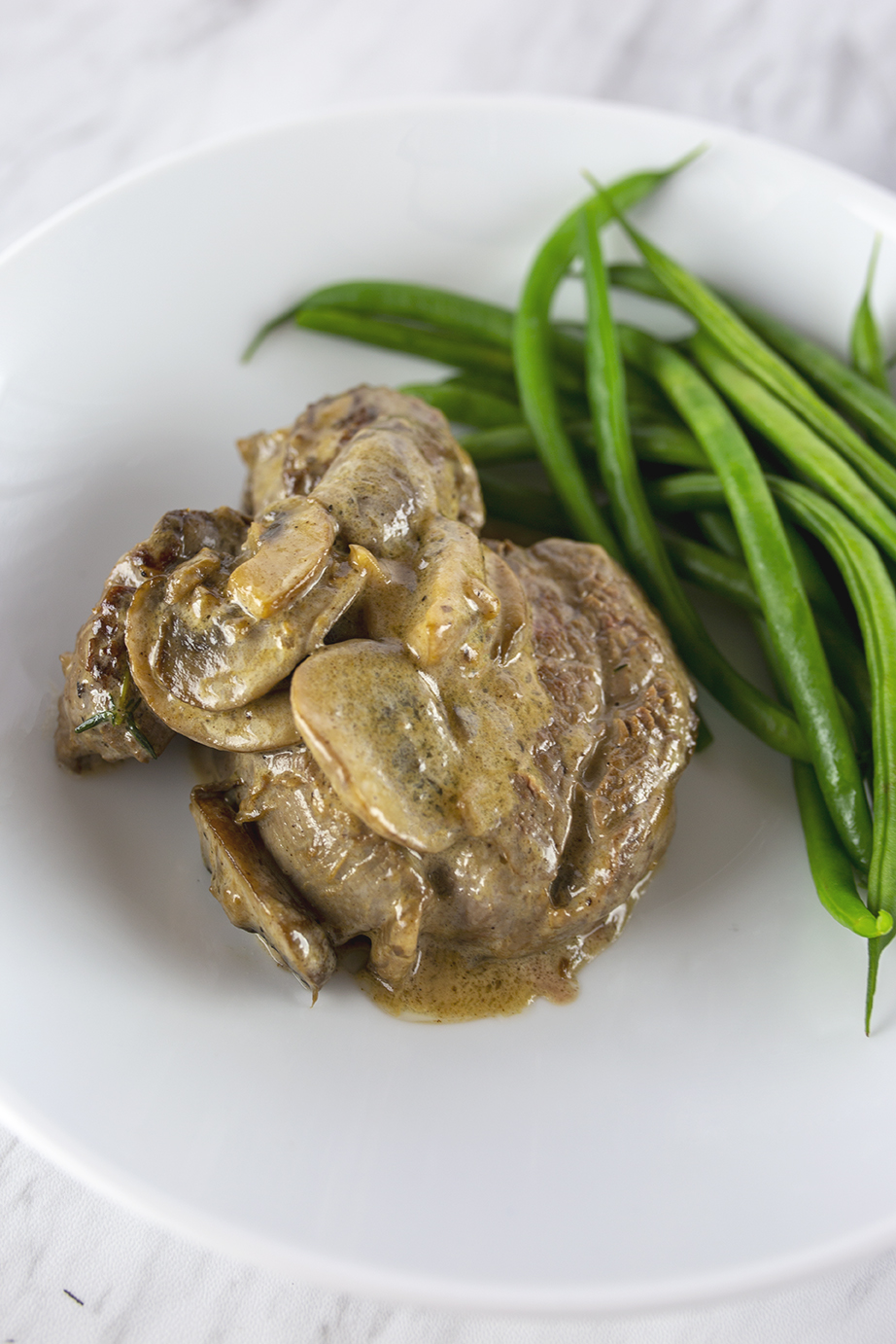 Steak tenderloin served with green beans topped with mushroom sauce on a white plate.