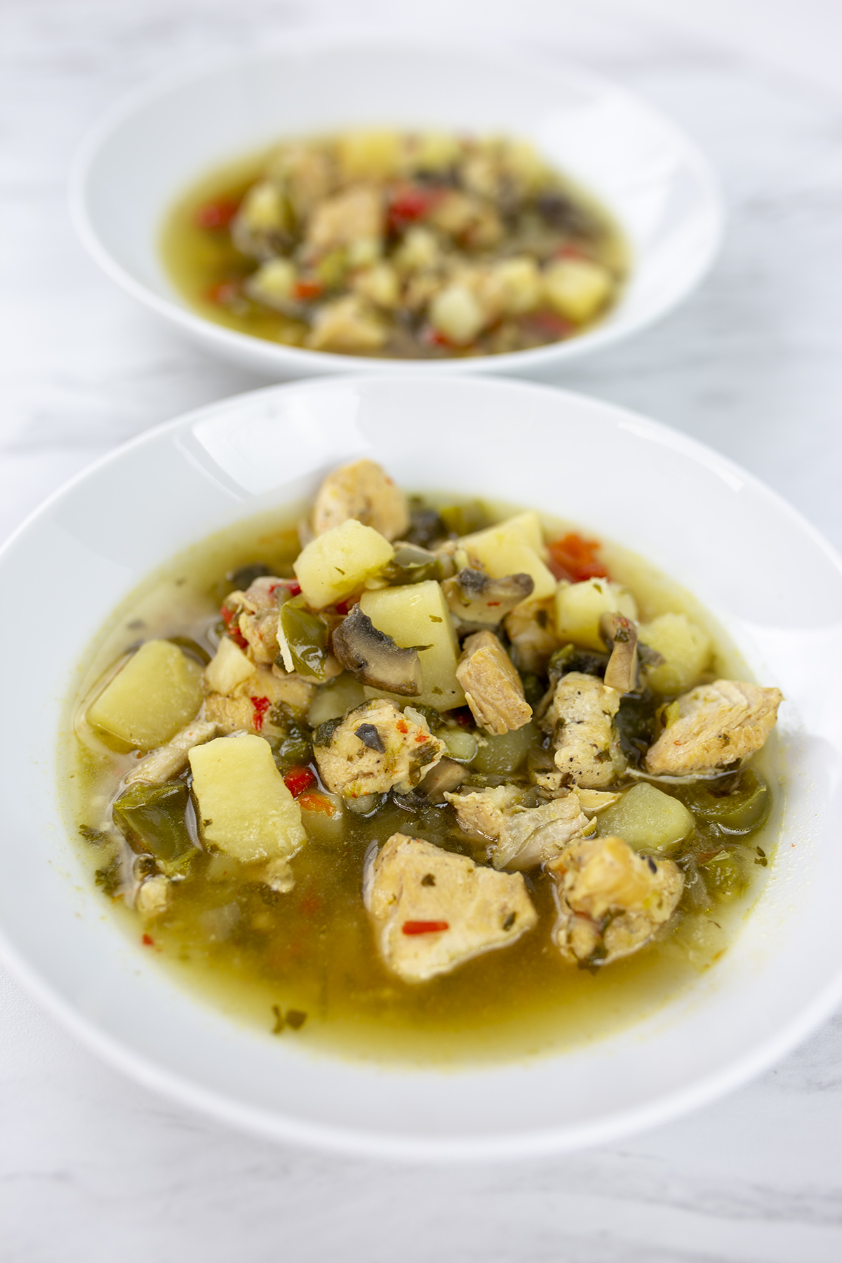 chicken soup with potatoes, mushrooms and broth on white bowls
