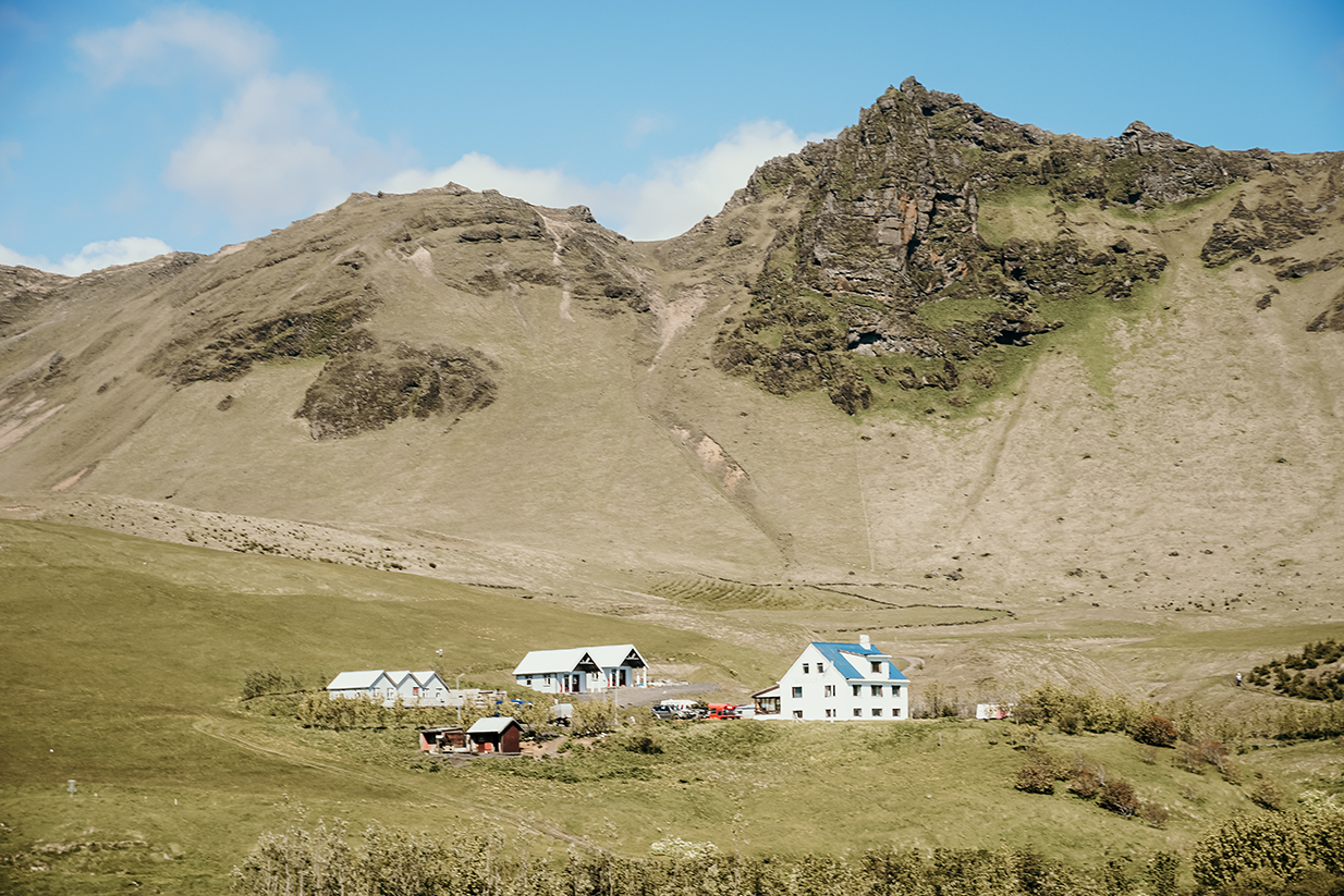 Houses at the bottom of a mountain face in Vik Iceland