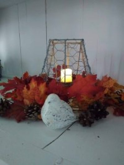 Chicken wire votive surrounded by fall leaves.