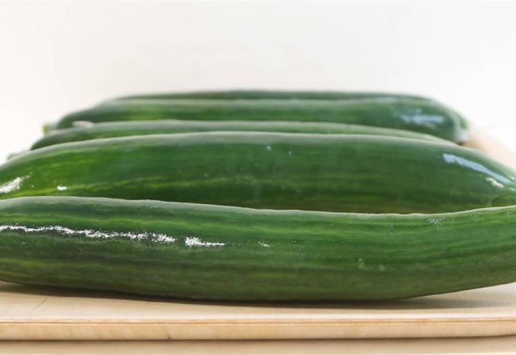 Cucumbers covered in bio-based material on a wooden tray.