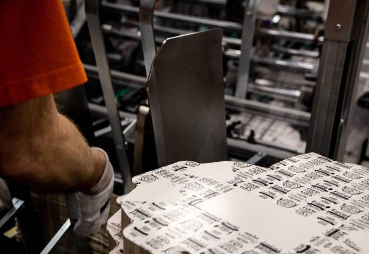 A pile of foldable cardboard packaging at the end of a production line in a factory.