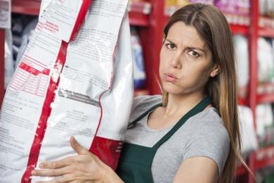 girl lifting dog food bag