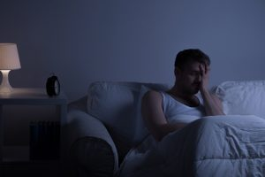 Person sits on sofa in dark room, covering eyes with one hand