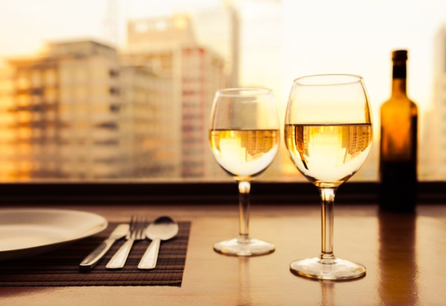 Two glasses of wine next to place setting on table