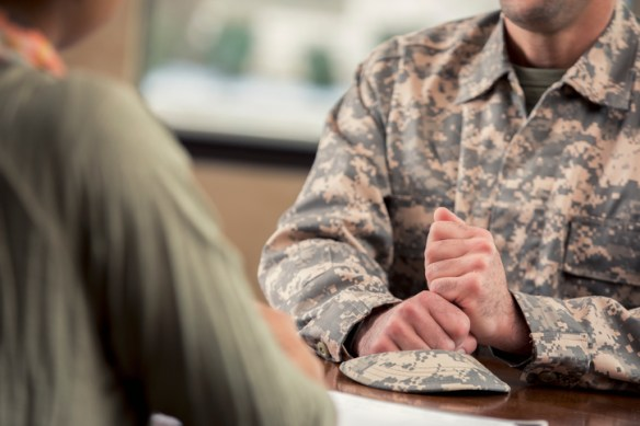 A man in uniform wrings his hands as he speaks to an unseen person.