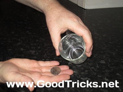 Image showing coin being swirled in glass and tipped out for examination by the audience.