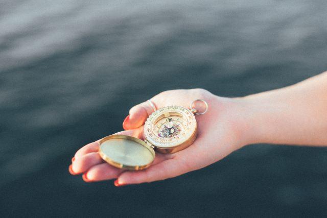 giving compass in hand