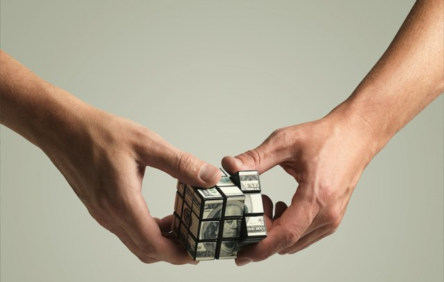 Money Rubix cube being twisted by haneds