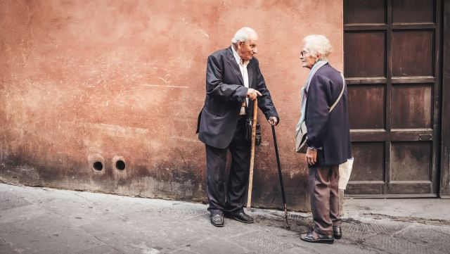 two seniors speaking on sidewalk