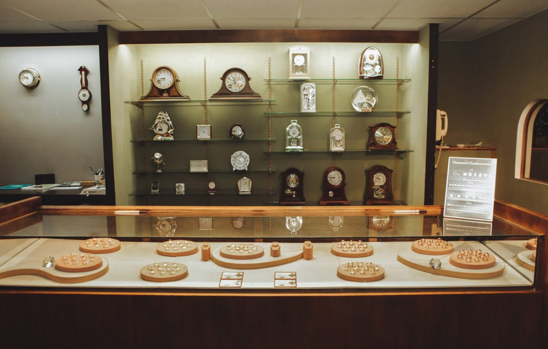 glass dispay of rings infront of shelves with watches