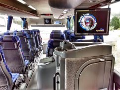 Luxury coach interior showing video screens and onboard WC