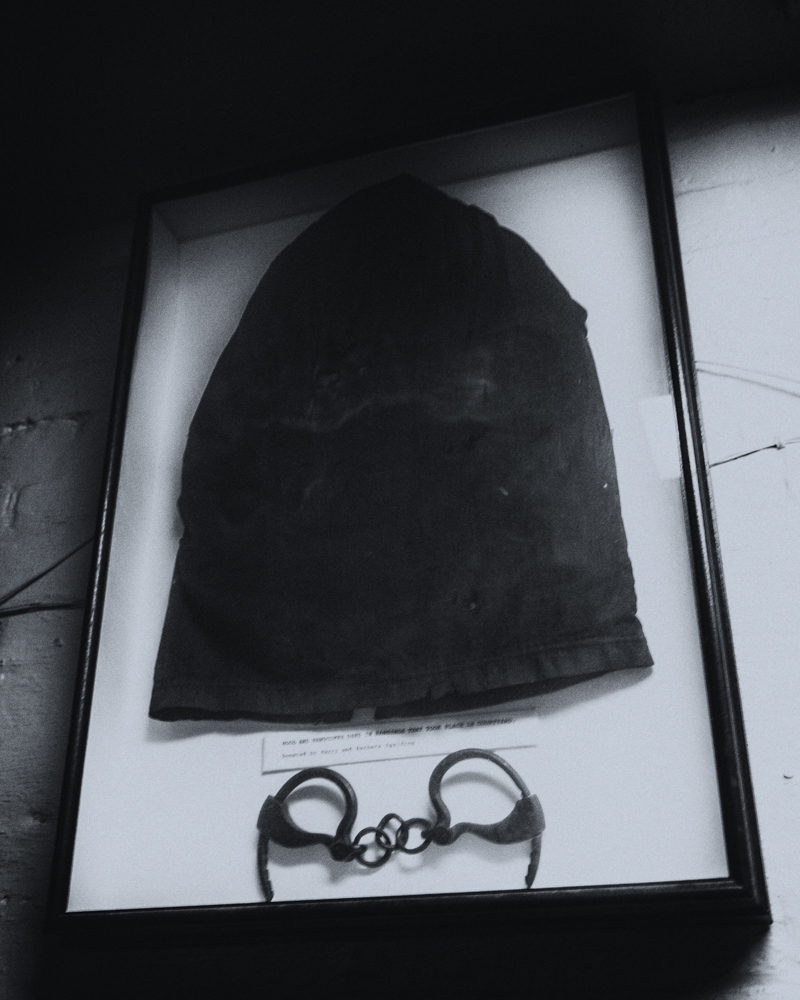 Hood placed over the head prior to hanging, and cuffs for the condemned on display at the Jailer's Inn.