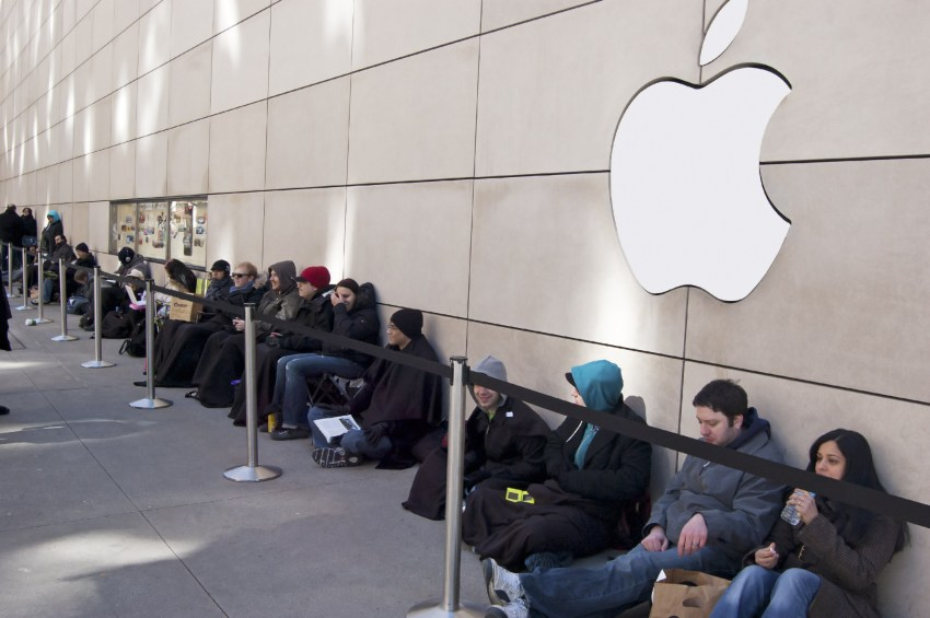Users wait in line to buy a new iPhone. jessicakirsh / Shutterstock.com