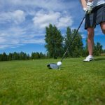 Image of woman golfer teeing off