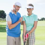 Man coaching woman golfer