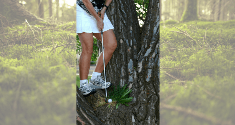 image of woman hitting golf ball in a tree