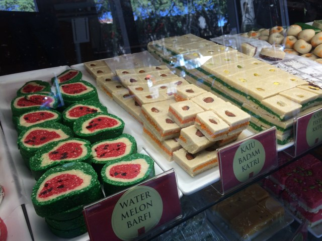 Trays of deserts like you'd see at a typical bakery in India.