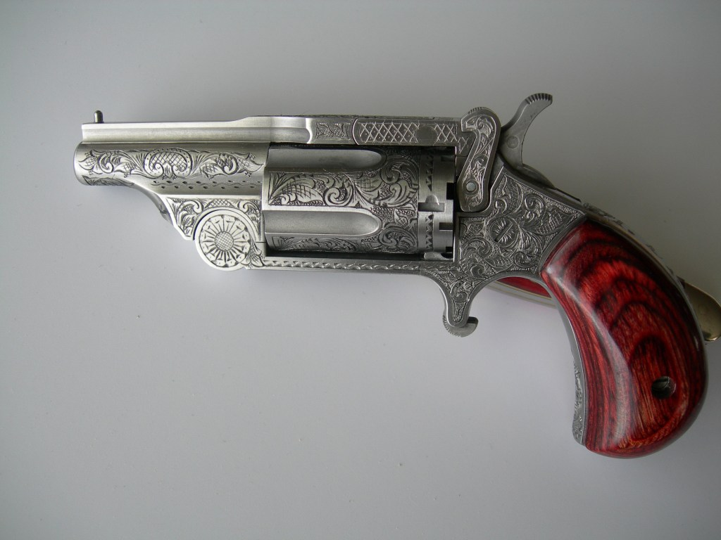 Full coverage American Scroll engraving on a Mini NAA Revolver. This gun is just about 3 inches long!