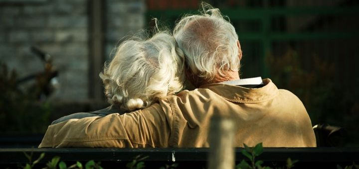 Elderly couple sitting on a bench from the back