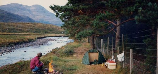 Man and tent wild camping by river with fire