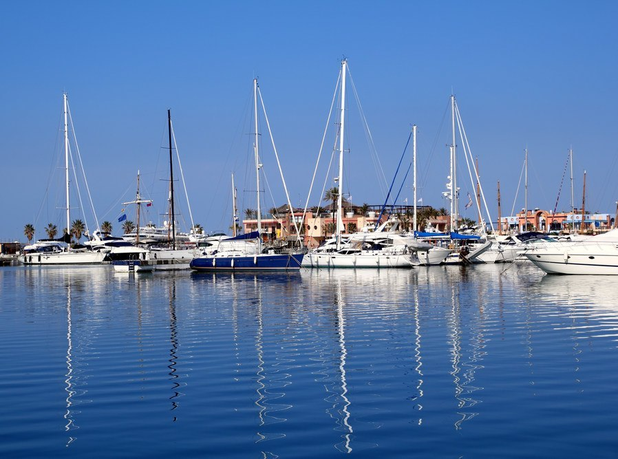 Boats in blue marina Mediterranean sea Denia ship poles reflection