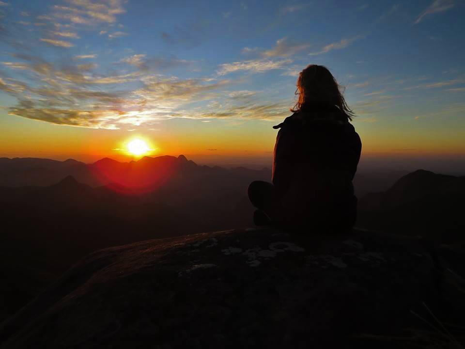 Fotografia colorida de uma pessoa sentada olhando o pôr do sol, que se destaca com seu centro amarelo e bordas laranjadas por entre um céu ainda azul com poucas nuvens e negras montanhas abaixo. Na contraluz, a silhueta da observadora de longos cabelos lisos.