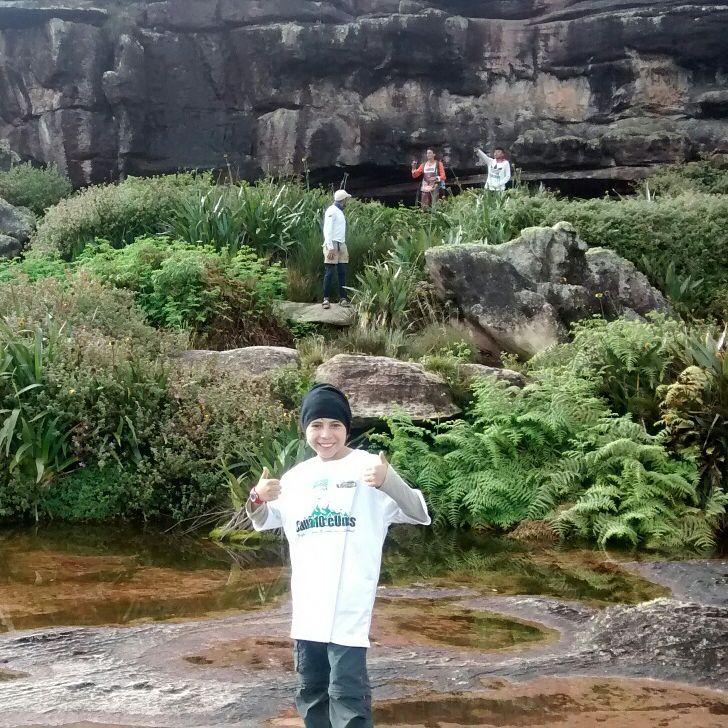 Cauã está no topo do monte Roraima. Ele está no centro da foto vestindo gorro, camiseta branca e calça. Sorri e faz sinal de jóia com as duas mãos. Atrás de Cauã estão algumas poças de água, vegetação baixa e verde e mais ao fundo, uma parede rochosa.