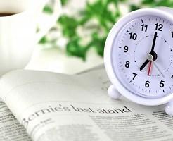 朝、真覚まし時計、新聞、コーヒー