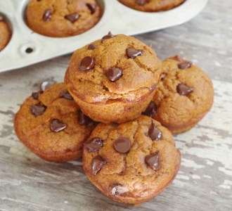 Stacked Pumpkin Chocolate Chip Muffins on a cutting board.