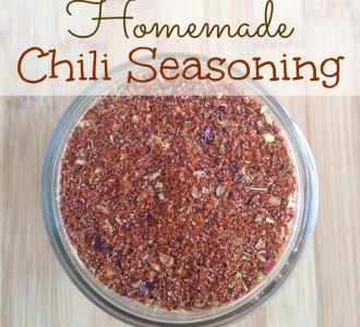 Homemade Chili Seasoning in mason jar on wooden cutting board.