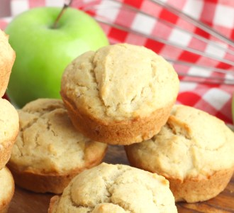Applesauce muffins sitting on a pile with green apples in the background.