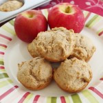Cinnamon Applesauce Muffins on a white plate with two red apples.