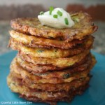 Finished fritters stacked on blue plate with a dollop of sour cream and green onions sprinkled on top.