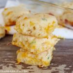 Three Cheddar and Green Onion Biscuits in a stack.