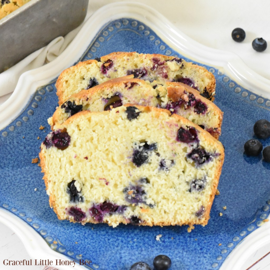 Slices of fresh baked blueberry bread on a blue plate.