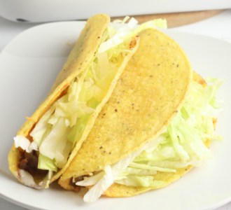 Two beef tacos topped with lettuce sitting on a white plate.