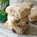 Three cinnamon raisin biscuits stacked on a wooden board with a 7-Up can in the background.