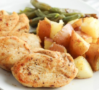 Cooked Cajun chicken, green beans and roasted potatoes on a white dinner plate.