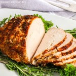 Air Fryer Turkey Breast, sliced on a white platter surrounded by fresh herbs.