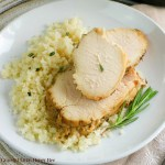 Tender, juicy turkey breast served on a whilte plate over rice garnished with fresh Rosemary.