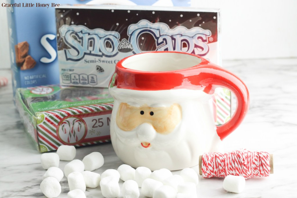Empty Santa Mugi with marshmallows, candy canes, chocolate candy and hot choclate sitting next to it.