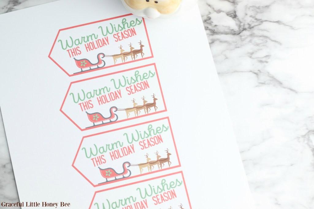 Printed gift tags for Santa Mug Gifts sitting on a marble countertop.