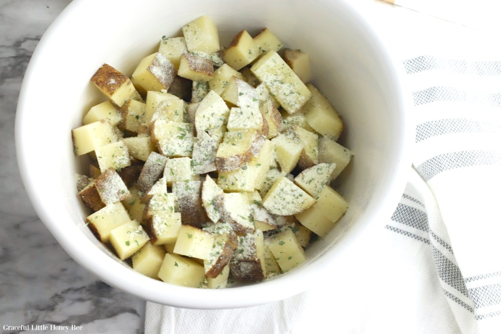 Diced potatoes in a white bowl with ranch seasoning on top.