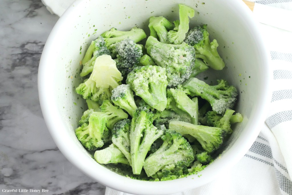Broccoli florets in a bowl with seasoning.